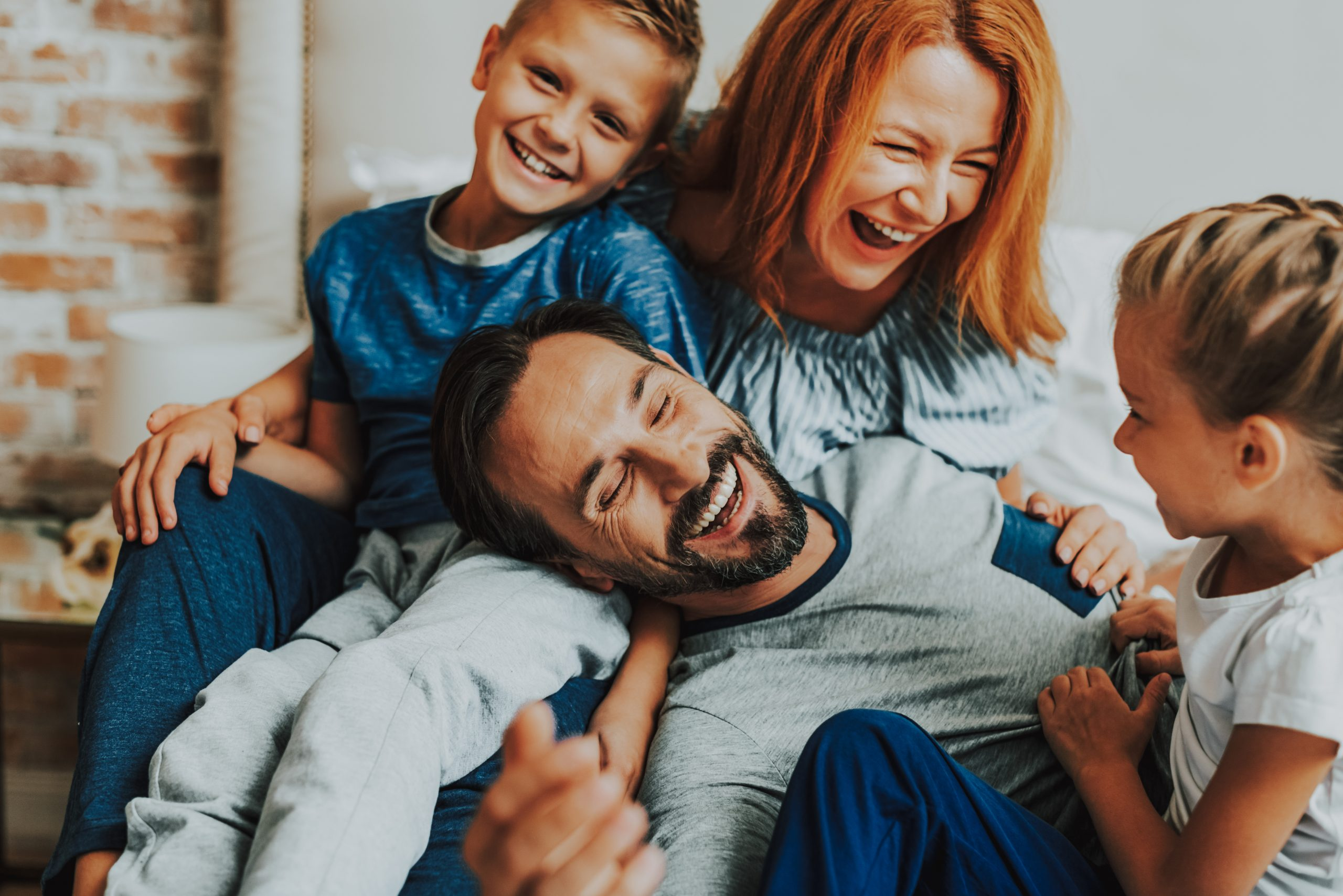 Family relationship concept. Close up portrait of happy father, mother and two their children laughing together while laying in bed in the morning