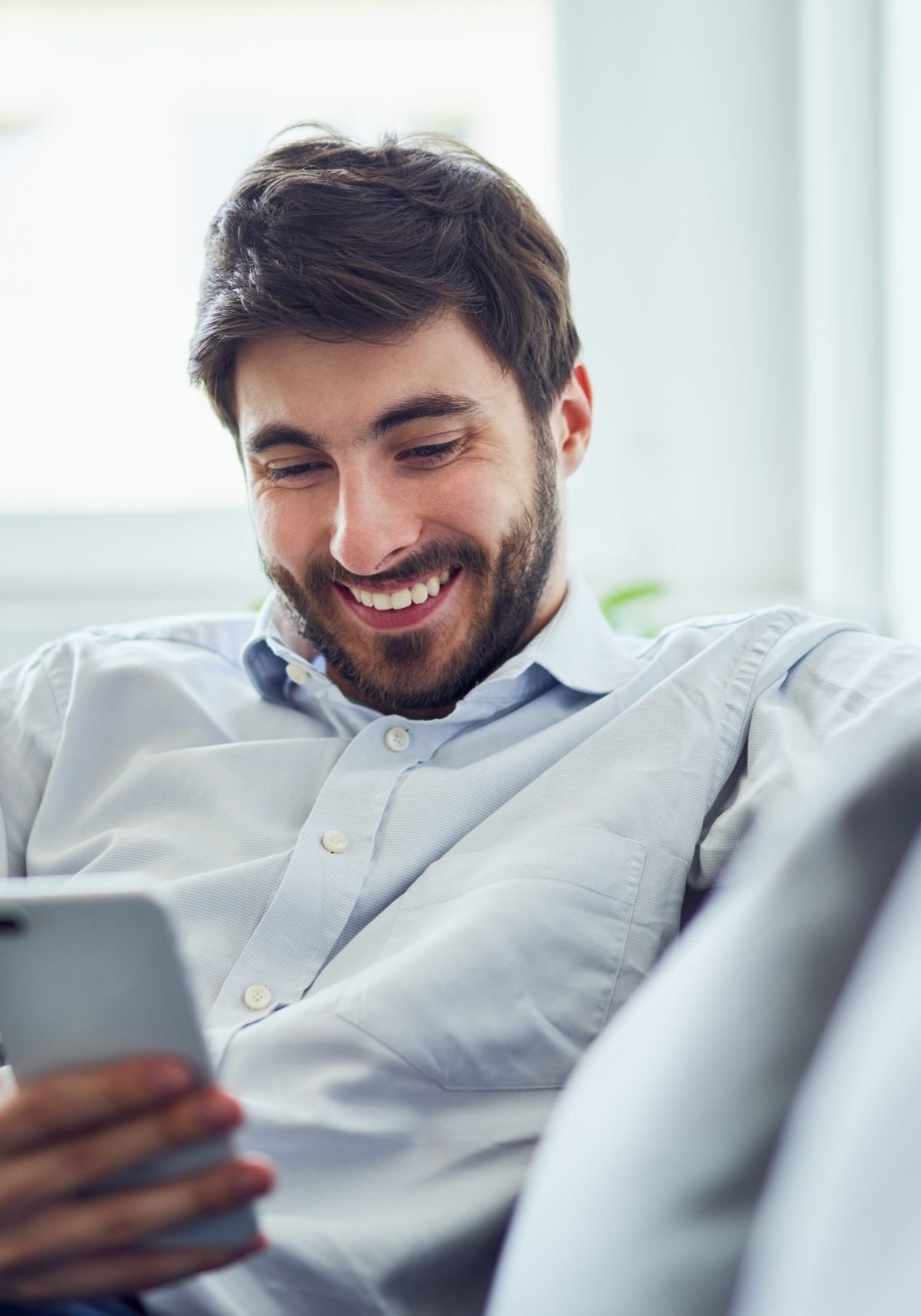 Cheerful young man using phone while relaxing on sofa after work